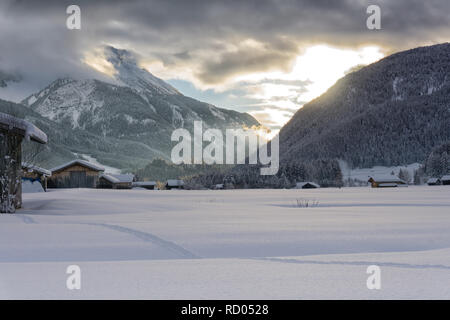 Winter mountain landscape at dusk. The setting sun illuminates dark clouds. Fog is falling in the valley. - Stock Photo