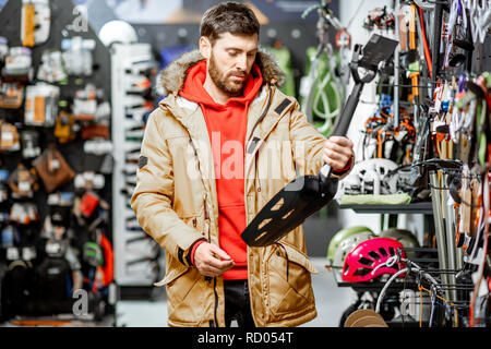 Man in winter jacket choosing mountaineer equipment holding snow shovel in the sports shop - Stock Photo