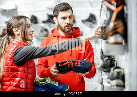 Mam and woman in red sports clothes choosing trail shoes for hiking standing near the showacase of the modern sports shop