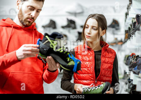 Man and woman looking on the studded shoes for hiking on the ice standing in the modern sports shop