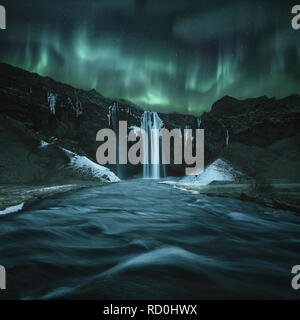 Northern lights over Seljalandsfoss waterfall at night, Iceland - Stock Photo