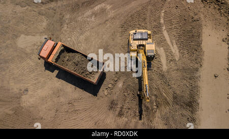 Aerial photo of excavator pours sand into the truck. - Stock Photo