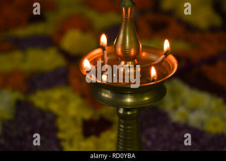 Flower bed decoration, floral pattern with lighted oil lamp on Onam, Vishu harvest festival of Kerala, India. - Stock Photo