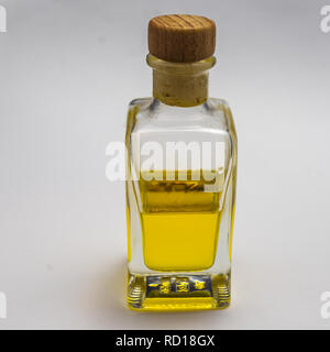 Transparent rectangular glass bottle with a cork stopper. Half filled with a yellow luminous liquid, exposed against a white background. - Stock Photo