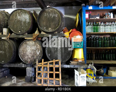 Cider barrels & bottles for apple juice on a farm, Aveton Gifford, South Hams, Devon. UK - Stock Photo