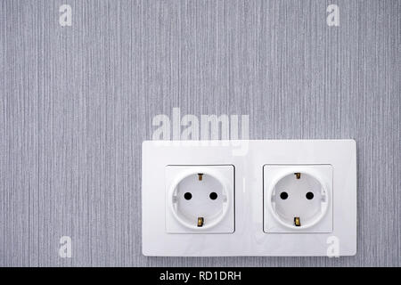 Two power sockets on gray wall. Close-up. - Stock Photo