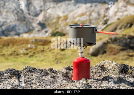 Tourist equipment and tools: camping gas over Marmolada mountain background Dolomites Italy - Stock Photo