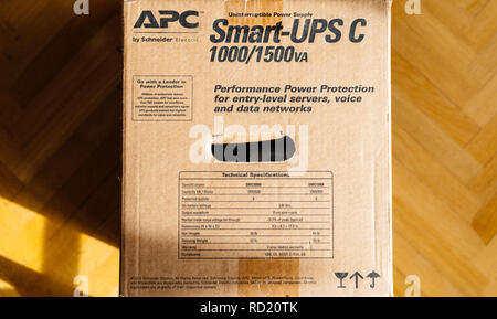 PARIS, FRANCE - MAR 29, 2018: Box of APC Smart-UPS C 1000VA LCD 230V enterprise-level uninterruptible power supplies made by American Power Conversion on office wooden floor - Stock Photo