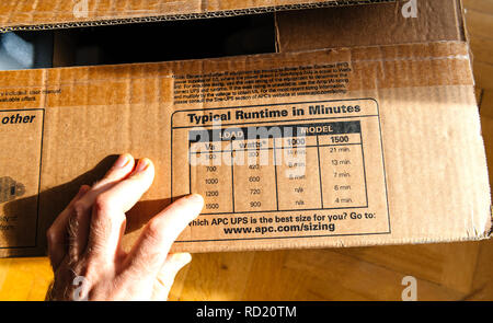 PARIS, FRANCE - MAR 29, 2018: POV on typical runtime in minutes enterprise-level uninterruptible power supplies made by American Power Conversion on office wooden floor - Stock Photo