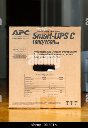 PARIS, FRANCE - MAR 29, 2018: APC Smart-UPS C 1000VA LCD 230V enterprise-level uninterruptible power supplies made by American Power Conversion on office wooden floor - Stock Photo