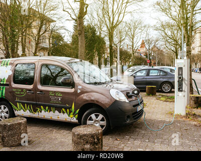 STRASBOURG, FRANCE - CIRCA 2018: Side view of plugged in Renault mini-van electric car on the street electric car charging station recharging slowly on the street in France  - Stock Photo