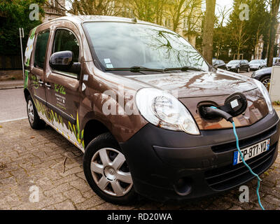 STRASBOURG, FRANCE - CIRCA 2018: Modern technology - Plugged in Renault mini-van electric car on the street electric car charging station recharging slowly on the street in France  - Stock Photo