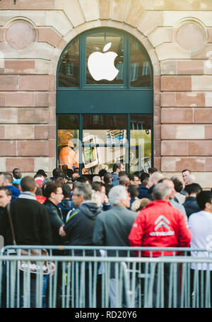 STRASBOURG, FRANCE - SEP, 19 2014: Group of young people in line queue in front of Apple Store with customers waiting in line to buy the latest iPhone iPad Apple Watch and notebook - Stock Photo