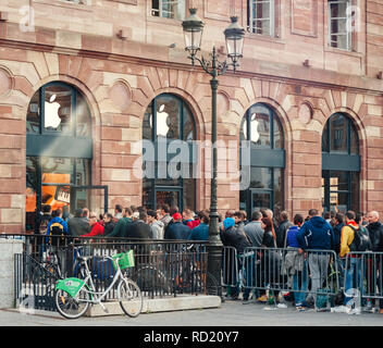 STRASBOURG, FRANCE - SEP, 19 2014: Crowd in line queue in front of Apple Store with customers waiting in line to buy the latest iPhone iPad Apple Watch and notebook - Stock Photo