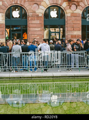 STRASBOURG, FRANCE - SEP, 19 2014: Impatient young people in line queue in front of Apple Store with customers waiting in line to buy the latest iPhone iPad Apple Watch and notebook - Stock Photo
