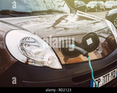 STRASBOURG, FRANCE - CIRCA 2018: Detail of plugged in Renault mini-van electric car on the street electric car charging station recharging slowly on the street in France sunlight flare  - Stock Photo