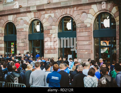 STRASBOURG, FRANCE - SEP, 19 2014: Adult and kids in line queue in front of Apple Store with customers waiting in line to buy the latest iPhone iPad Apple Watch and notebook - Stock Photo