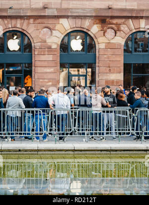 STRASBOURG, FRANCE - SEP, 19 2014: Large crowd of people in line queue in front of Apple Store with customers waiting in line to buy the latest iPhone iPad Apple Watch and notebook - Stock Photo