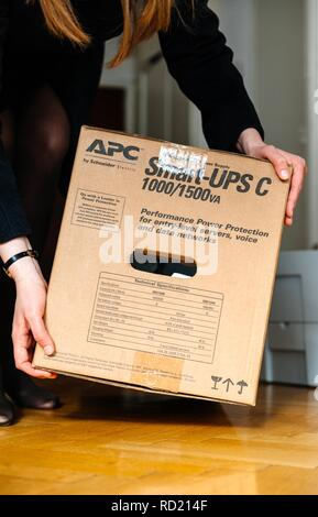 PARIS, FRANCE - MAR 29, 2018: IT woman unboxing APC Smart-UPS C 1000VA LCD 230V enterprise-level uninterruptible power supplies made by American Power Conversion office wooden floor - Stock Photo