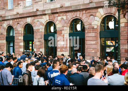 STRASBOURG, FRANCE - SEP, 19 2014: Young people in line queue in front of Apple Store with customers waiting in line to buy the latest iPhone iPad Apple Watch and notebook - Stock Photo