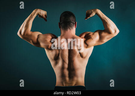 Rear view of a perfect muscular young man without a shirt. - Stock Photo