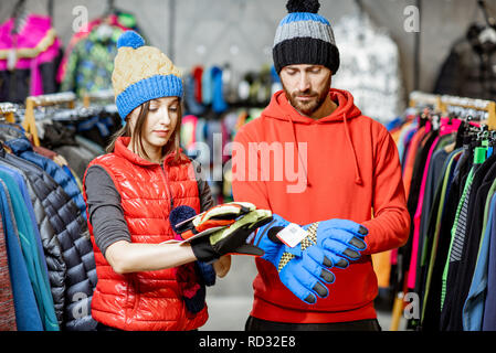Young couple trying winter clothes wearing colorful hats and gloves in the sports shop - Stock Photo