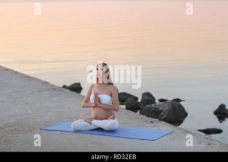 Beautiful pregnant woman doing yoga at the seaside - Stock Photo