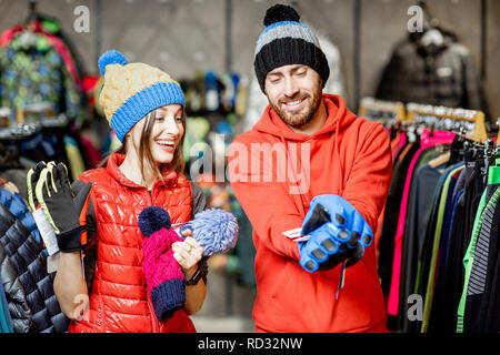Young and happy couple trying winter clothes wearing colorful hats and gloves in the sports shop - Stock Photo
