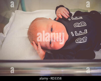 Newborn baby boy in hospital crib
