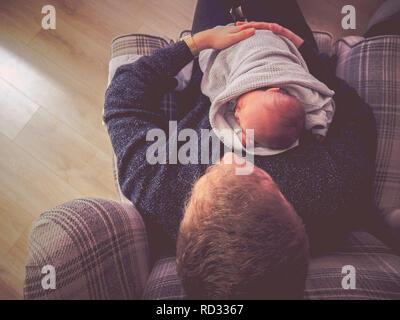 Newborn baby boy cuddling father