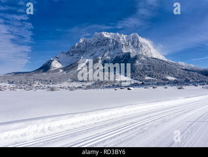 The Zugspitze Massif from the valley of Ehrwald in sunny winter day, groomed ski trails in foreground. Winter mountain landscape. - Stock Photo