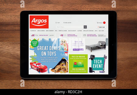 The website of Argos is seen on an iPad tablet, which is resting on a wooden table (Editorial use only). - Stock Photo