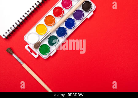 Watercolor paints and brushes with canvas for painting with copyspace on red background