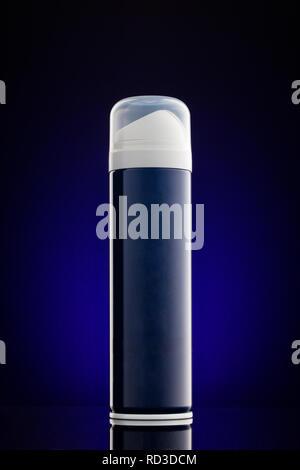 Closeup shot of blue deodorant perfume can against dark blue background. - Stock Photo