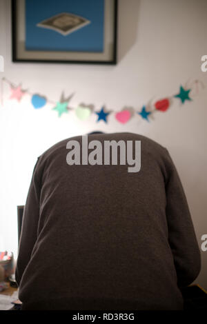 adult male in grey sweater, leans forward to look through his record collection in his flat - Stock Photo