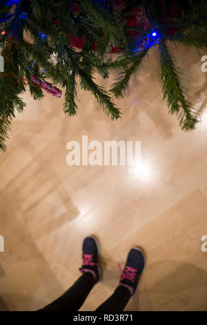 a cropped view of kids feet standing near a decorated christmas tree inside a home - Stock Photo