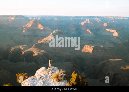 A male photographer is standing on a cliff taking in the amazing view over famous Grand Canyon National Park at sunset, American Southwest, USA - Stock Photo