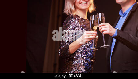 Picture of woman in brilliant dress and men with wine glasses with champagne on black background - Stock Photo
