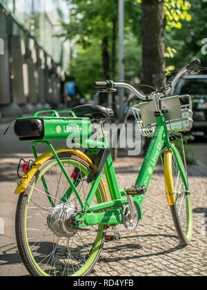 BERLIN, GERMANY - JULY 2018: A Lime-E electric bike on a sidewalk in Berlin, Germany - Stock Photo