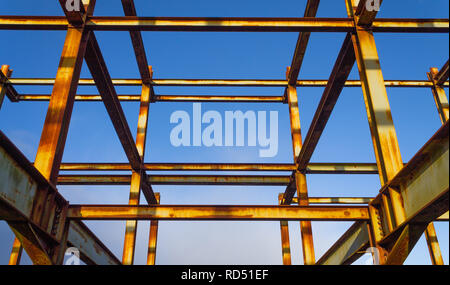rusting rolled steel joist skeleton of a building outlined against a blue sky - Stock Photo