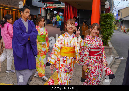 Young smiling Japanese girls in traditional kimono dresses. A Japanese man in traditional dress can be seen on the left. Photographed at the Fushimi I - Stock Photo