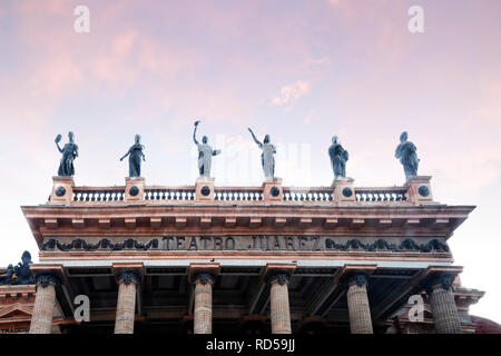 Guanajuato, Guanajuato  Mexico -10/18/2018: Upper half of the front of Theatro Juarez, with columns and Greek muses statues, and a pink sky. - Stock Photo