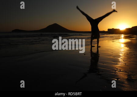 Girl doing a cartwheel on the beach at sunset - Stock Photo