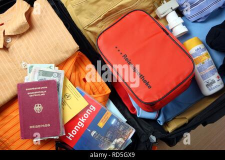 Holiday luggage, first-aid kit, passport, vaccination card, travel guide - Stock Photo