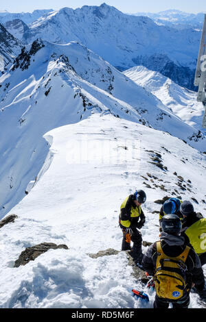 Mountain rescue team in training on the summit of Aiguille Rouge, with the Mont Blanc massif behind them. - Stock Photo