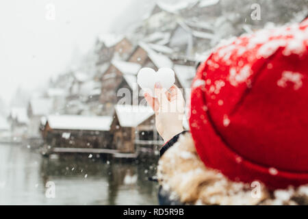 Young blonde woman in a red hat holding snow ball in a shape of a heart in front of the old village of Hallstatt, Austria. Blurry background, shallow  - Stock Photo