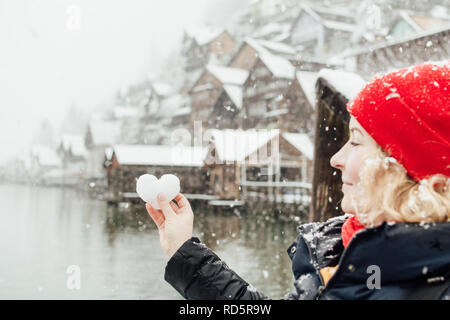 Young blonde smiling woman in a red hat holding snow ball in a shape of a heart in front of the old village of Hallstatt, Austria. Blurry background,  - Stock Photo