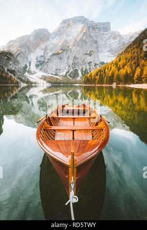 Beautiful view of traditional wooden rowing boat on scenic Lago di Braies in the Dolomites in scenic morning light at sunrise, South Tyrol, Italy - Stock Photo