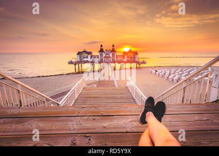 Young man sitting on wooden pier enjoying beautiful sunrise at famous Seebrucke Sellin at Ostseebad Sellin, island of Ruegen, Baltic Sea, Germany - Stock Photo