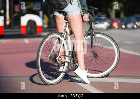 female cyclist waiting at the traffic light - Stock Photo